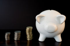Piggy bank and coins. White piggy bank isolated on black background with coins Royalty Free Stock Photo