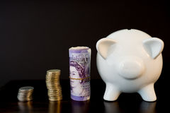 Piggy bank and coins. White piggy bank isolated on black background with coins royalty free stock photos