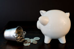 Piggy bank and coins. White piggy bank isolated on black background with coins Royalty Free Stock Images