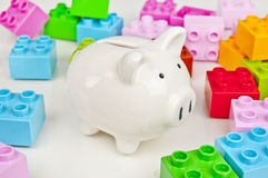 Piggy bank and colorful toy bricks. Saving on toys. Stock Photos