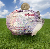 Piggy bank covered with British pounds Royalty Free Stock Photography
