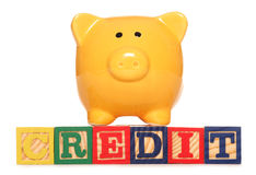 Piggy bank with credit text Royalty Free Stock Images