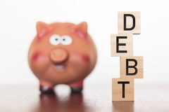 Piggy bank and debt word on wooden blocks