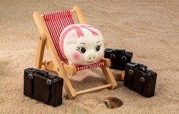 Piggy bank in a deck chair Stock Images