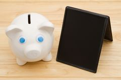 A piggy bank on a desk with chalkboard Stock Image
