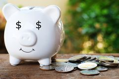 Piggy bank with dollar eye and pile of coin for saving money concept. Copy space stock photos