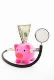 Piggy bank, dollar and stethoscope. Pink piggy bank using stethoscope facing to camera and dollar bill on its hole over white background stock photos