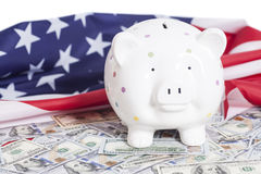 Piggy Bank on Dollars with American Flag Stock Photos