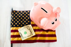 Piggy Bank on Dollars with American Flag. Pink Piggy Bank on Dollars with American Flag Stock Images