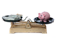Piggy bank and dollars on scale Stock Photo