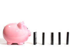 Piggy bank with dominoes Stock Photos