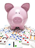 Piggy bank and dominos Stock Photos