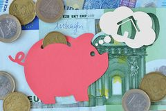 Piggy bank dreaming about house on euro banknotes and coins - Saving money for a house concept stock photo
