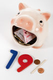 Piggy bank eating money Royalty Free Stock Photography