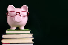 Piggy bank education savings concept, glasses and blackboard copy space Stock Photos