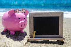 Piggy bank and empty black board on the beach Royalty Free Stock Image