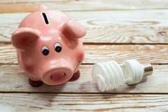 Piggy Bank and Energy Saving Bulb on Wooden Background Royalty Free Stock Images