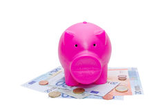Piggy bank on euro bank note and coins Royalty Free Stock Photography