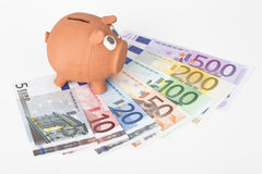Piggy bank with euro banknotes Stock Images