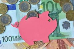 Piggy bank on euro banknotes and coins - Saving money concept. Piggy bank on euro banknotes and coins. Saving money concept royalty free stock image