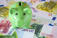 Piggy Bank on Euro banknotes. Green Piggy Bank on a background made of Euro banknotes Royalty Free Stock Photography