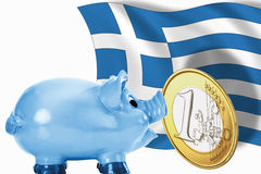 Piggy bank with 1 euro coin and greek flag Royalty Free Stock Photo