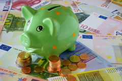 Piggy Bank on Euro money Background. Green Piggy Bank on a background made of Euro banknotes und coins Stock Image
