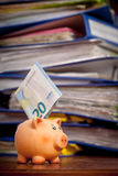 Piggy bank with euro note against stack of folders Stock Images