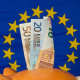 Piggy bank with euro notes, EU flag in the background Royalty Free Stock Photo