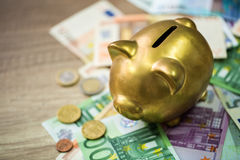 Piggy bank with euro on wooden table Royalty Free Stock Images