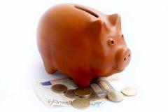 Piggy bank with euros. Piggy bank placed over euros, economy and savings concept Royalty Free Stock Photos