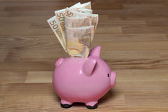 Piggy bank with euros. On wooden background Royalty Free Stock Image
