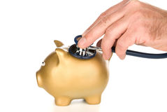Piggy bank examined with stethoscope Royalty Free Stock Images