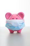 Piggy Bank with Face Mask - Swine Flu Concept. Pink piggy bank wearing a protective face mask. Concept for protection, flu, virus, sickness Royalty Free Stock Image