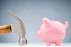 Piggy Bank Facing a Hammer Stock Image