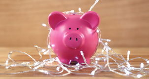 Piggy bank with fairy lights on wooden table stock footage