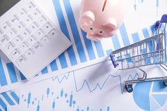 Piggy bank, financial graphs and shopping cart. Business concept stock images