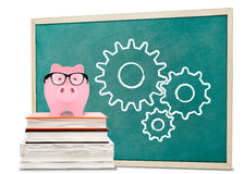 Piggy bank and gears drawnings on blackboard Stock Photos