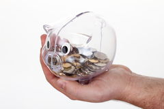 Piggy bank in glass with coins on hand. On white Royalty Free Stock Image