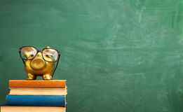 Piggy bank with glasses on books Royalty Free Stock Images