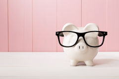 Piggy bank with glasses over pink wooden wall Royalty Free Stock Images