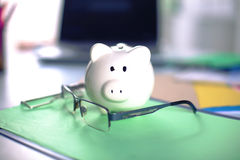 Piggy bank with glasses on the table Royalty Free Stock Photography