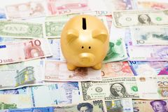 Piggy bank on global different currency Stock Photography
