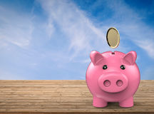 Piggy bank with gold coin falling Stock Image