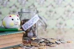 The piggy bank and a green pencil are placed on the hardback wit. H a pile of coins on a wooden table. The concept of intelligence comes from education Stock Photos