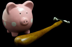 Piggy Bank With Hammer. Pink polka dot piggy bank with hammer on black background Royalty Free Stock Photography
