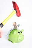 Piggy bank and hammer. Green piggy bank and hand with hammer Stock Image