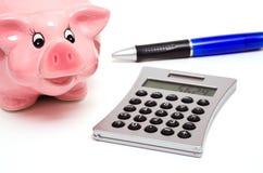 Piggy bank and a hand calculator Royalty Free Stock Photos