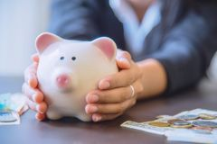 Piggy bank in hand with cash pile. Stock Photos