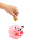 Piggy bank and hand with coin Royalty Free Stock Image